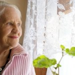 Elderly woman looks out her window smiling